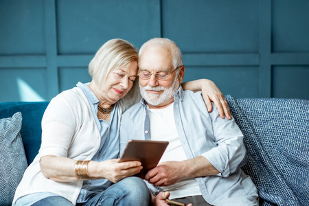 Schönes Seniorenpaar lässig gekleidet mit digitalem Tablet, während es zu Hause auf der bequemen Couch sitzt sitting Standard-Bild