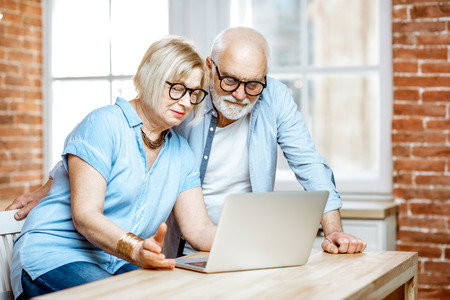 Happy senior couple shopping online using credit card and laptop at home