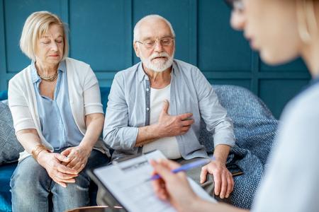 Senior pareja sentada con la enfermera durante la consulta médica, preocupada con dolor de corazón en la oficina