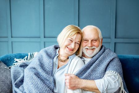 Porträt eines reizenden Seniorenpaares, das sich gemütlich und warm fühlt und zu Hause mit Plaid eingewickelt auf der Couch sitzt