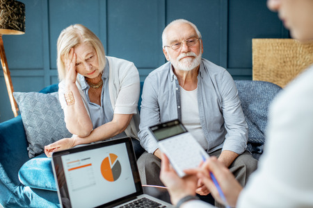 Älteres Paar mit traurigen Emotionen während des Treffens mit dem Finanzberater, das im Büro eine Vereinbarung unterzeichnet Standard-Bild