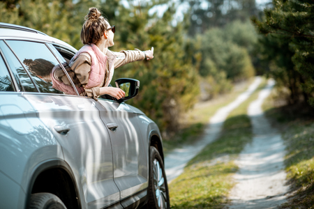 Young woman enjoying the trip, looking out the car window on a picturesque road in the woods