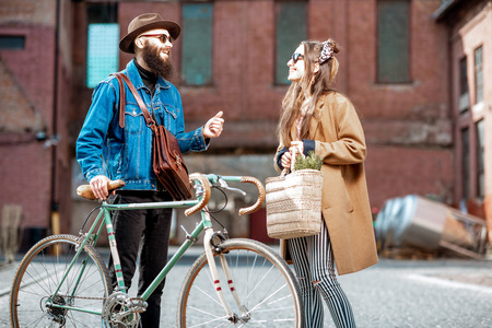 Stylish young man and woman having a conversation standing together with retro bicycle outdoors on the industrial urban background