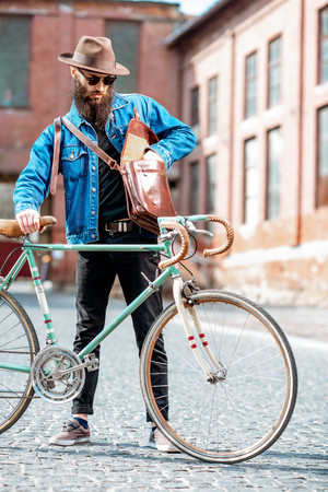 Lifestyle portrait of a bearded hipster dressed stylishly with hat and jacket standing with retro bicycle on the urban background