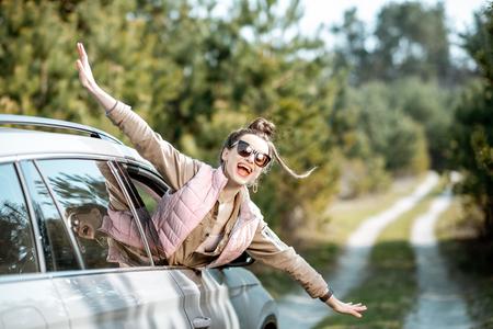 Mujer joven disfrutando del viaje, mirando por la ventana del coche en una pintoresca carretera en el bosque