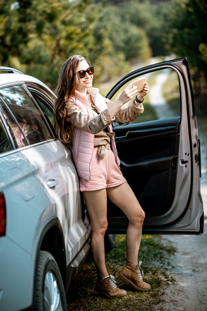Young woman traveler enjoying the trip, standing with phone near the car door on a picturesque road in the woods Stock Photo