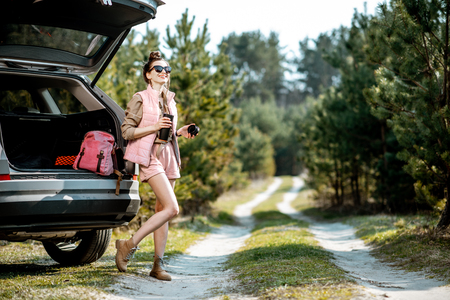 Young woman traveler enjoying the trip, standing with hot drink near the car trunk on a picturesque road in the woods