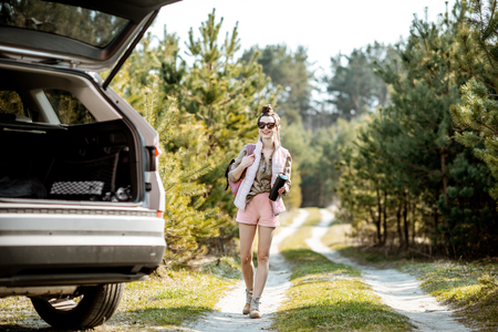 Young woman traveler walking on a picturesque road, traveling by car in the forest