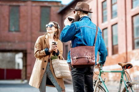 Stylish young man and woman having fun, standing together with retro bicycle outdoors on the industrial urban background