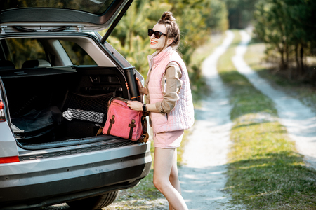 Young woman traveler enjoying the trip, standing near the car trunk on a picturesque road in the woods