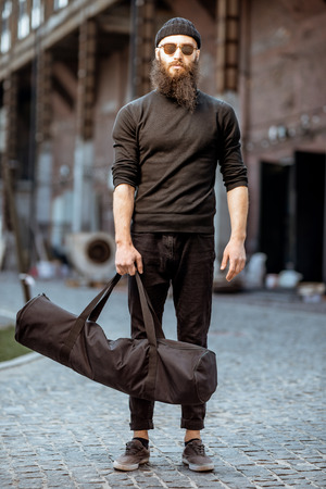 Portrait of a serious bearded man as a killer dressed in black tight clothes holding bag with weapons outdoors on the industrial background