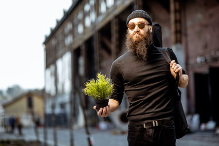 Portrait of a serious bearded man as a killer dressed in black tight clothes holding flower pot and bag with weapon outdoors