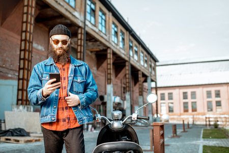 Lifestyle portrait of a bearded hipster standing with phone near the retro moped outdoors on the industrial urban background Foto de archivo