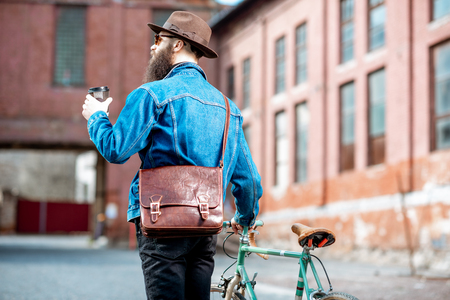 Stylish hipster walking with coffee and retro bicycle on the industrial urban background, back view
