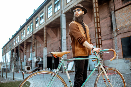 Lifestyle portrait of a bearded hipster dressed stylishly walking with retro bicycle on the industrial urban background