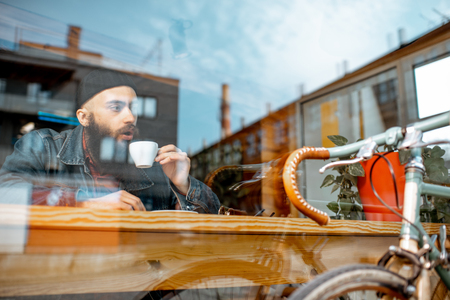 Stylish man enjoying a coffee drink while sitting at the cafe near the window with retro bicycle. View through the window with urban reflection 스톡 콘텐츠