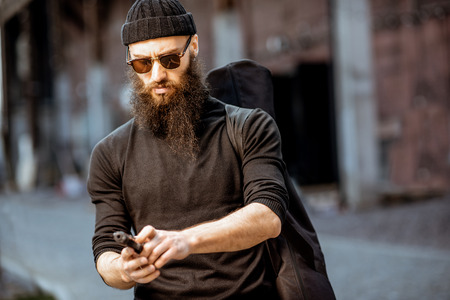 Serious bearded man dressed in black tight clothes as a killer standing with handgun outdoors on the industrial urban background
