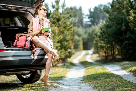 Young woman having a snack with lunch box while tarveling by car in the woods Imagens