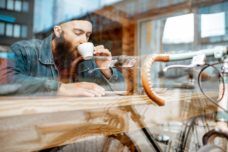 Stylish man enjoying a coffee drink while sitting at the cafe near the window with retro bicycle. View through the window with urban reflection Stock Photo