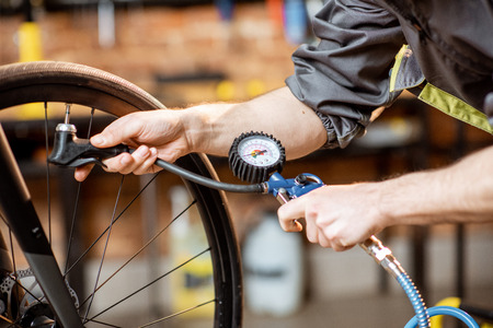 Repairman in workwear serving a sports bike, pumping wheels at the bicycle workshop