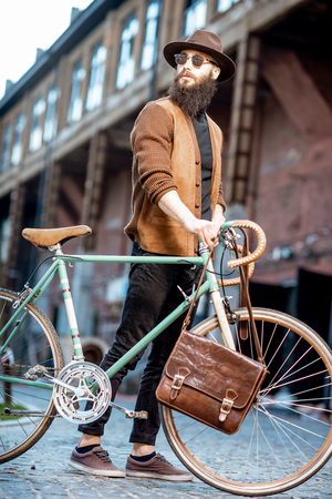 Bearded hipster dressed stylishly with hat standing with retro bicycle and bag outdoors on the urban background Foto de archivo