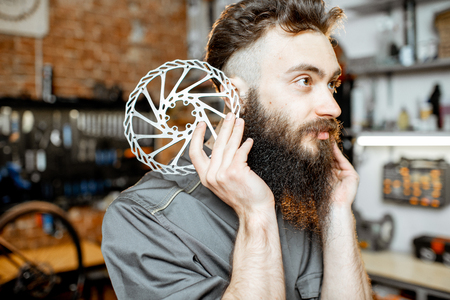 Portrait of a handsome bearded repairman in workwear with brake discs in the bicycle workshop
