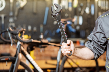 Repairman holding cleavage key in the bicycle workshop, close-up view