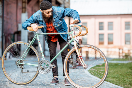 Lifestyle portrait of a bearded hipster dressed stylishly with hat and jacket standing with retro bicycle on the industrial urban background