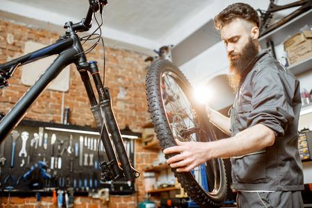 Reparador guapo en ropa de trabajo que sirve bicicleta de montaña, de pie con la rueda delantera en el taller de una tienda de bicicletas Foto de archivo