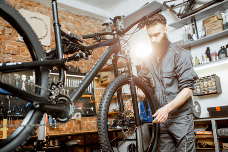 Handsome bearded repairman in workwear mounting wheel on a mountain bicycle at the workshop