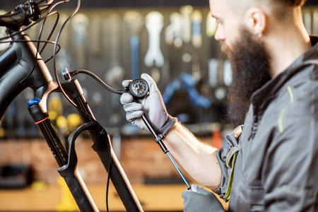 Repairman pumping shock absorber of the mountain bike in the workshop of the bicycle shop Stock Photo