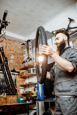 Handsome repairman in workwear serving mountain bicycle, standing with front wheel at the workshop of a bicycle shop