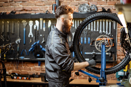 Bicycle service worker aligning wheel with special tool at the workshop of the bicycle shop