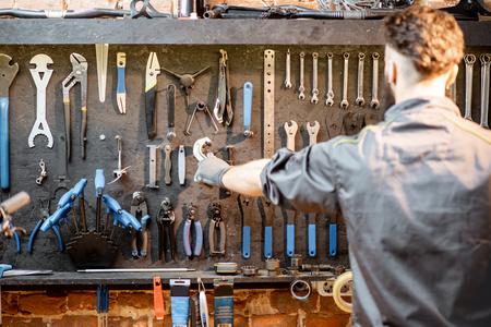 Mechaniker, der Schraubenschlüssel von der Wand mit verschiedenen Werkzeugen für die Fahrradreparatur im Innenbereich nimmt Standard-Bild