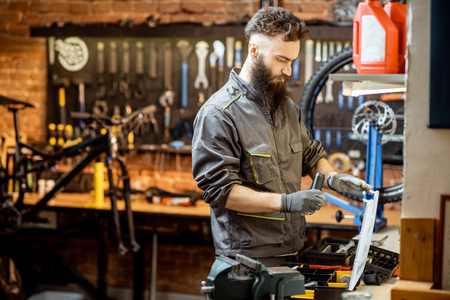 Handsome bearded repairman in workwear working in the beautiful bicycle workshop