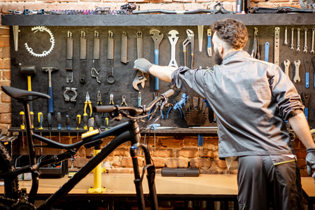 Repairman taking wrenches from the wall with different tools for bicycle repairing indoors Banco de Imagens