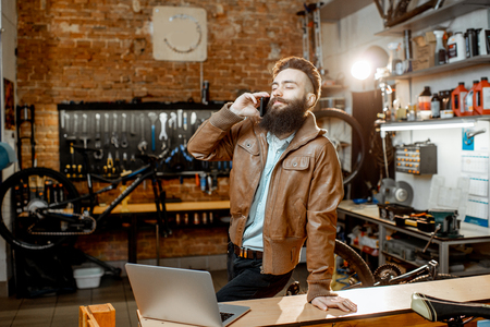 Businessman as a shop owner or manager talking with phone in the bicycle workshop