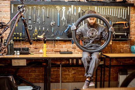 Portrait of a handsome repairman in workwear sitting with bicycle wheel at the workshop of a bike shop Standard-Bild