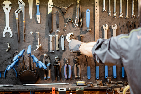 Man taking wrenches from the black wall with different tools for bicycle repairing