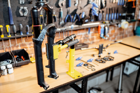 Bicycle fork during the repairing process hanging on a stand in the bicycle workshop