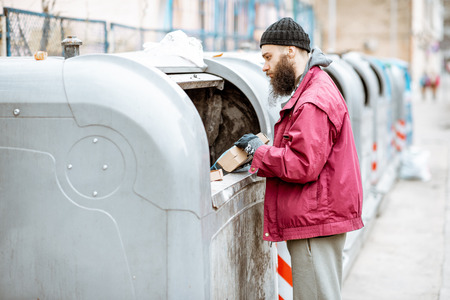 Homeless bearded beggar searching some food, rummaging in the trash in the city. Concept of poverty and unemployment Stock Photo