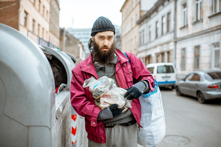 Portrait of a homeless bearded beggar standing with bag and some finded food near the trash containers in the city. Concept of poverty Stock Photo