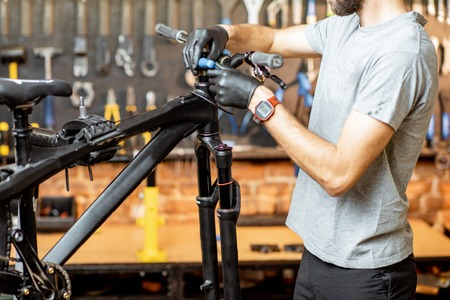 Man removing steering wheel from the bicycle at the workshop Stock Photo - 122205959