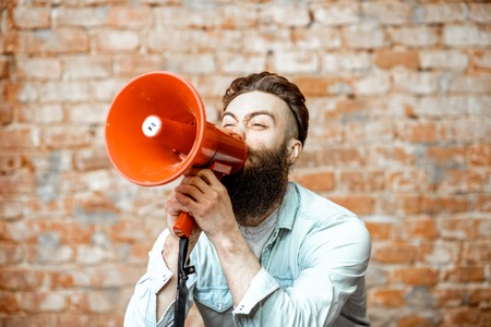 Handsome bearded man with red loudspeaker on the brick wall background
