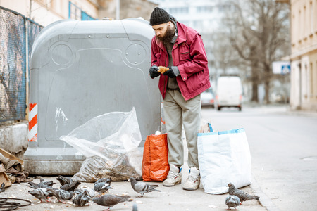 Portrait of a homeless bearded beggar feeding pigeons near the trash in the city. Concept of poverty and unemployment