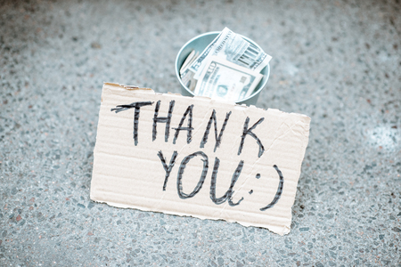 Beggars cup with money and cardboard with thank you message on the street
