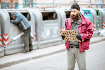 Portrait of a depressed homeless beggar standing on the street with social message on the cardboard. Concept of human poverty Stock Photo