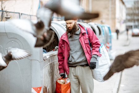 Portrait of a homeless depressed beggar standing with bags near the trash containers in the city. Concept of poverty and unemployment Фото со стока