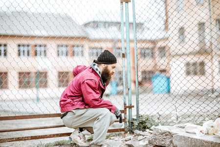 Portrait of a depressed homeless beggar or prisoner standing near the old metal fence outdoors