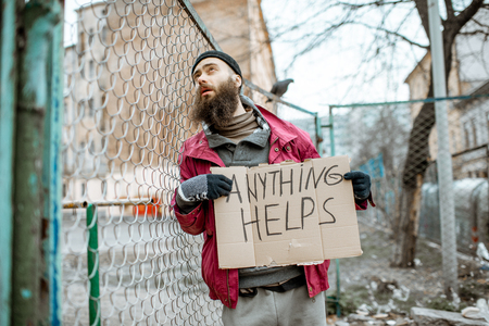Portrait of a depressed homeless beggar standing with social message on the cardboard near the old fence outdoors Stock Photo - 121320227